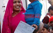 Residents of Jehangipuri slum district of North Delhi pick up a prescription from Save the Children's mobile clinic.